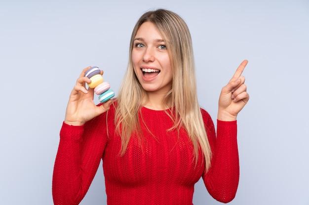 Jovem mulher loira sobre azul segurando macarons franceses coloridos e apontando uma ótima idéia