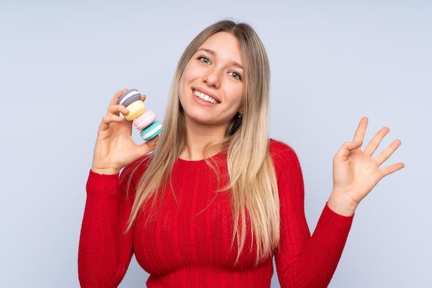 Jovem mulher loira sobre azul segurando macarons franceses coloridos e saudação