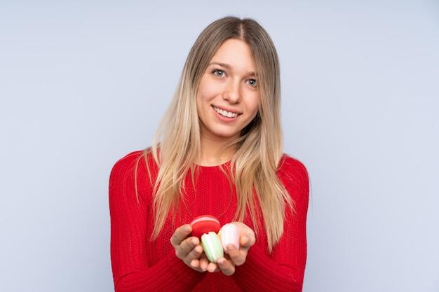 Jovem mulher loira sobre azul segurando macarons franceses coloridos