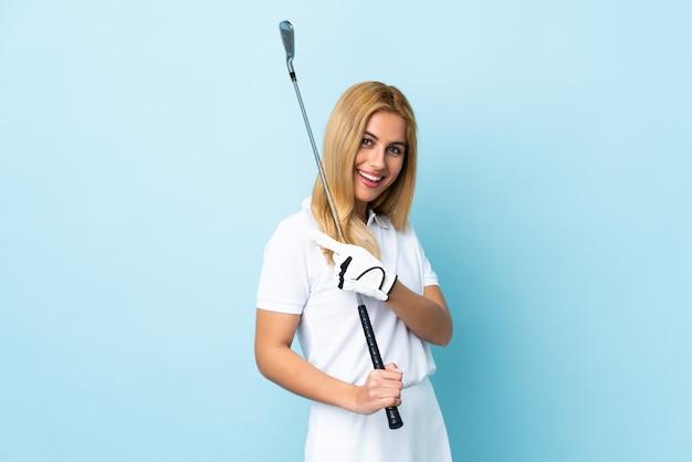 Jovem mulher loira sobre espaço azul isolado, jogando golfe e apontando para a lateral