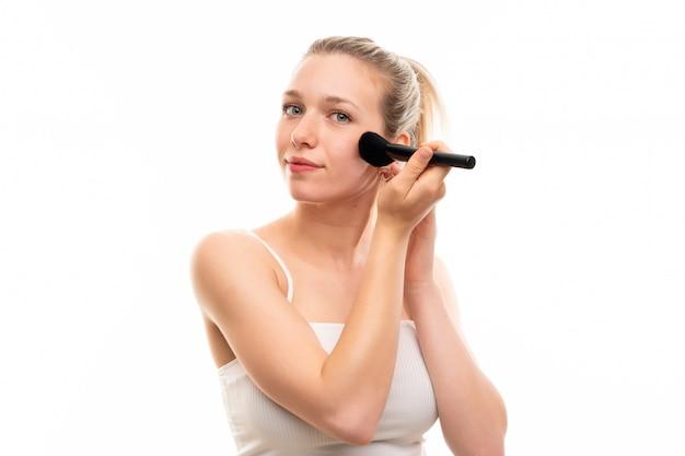 Jovem mulher loira sobre fundo branco isolado com pincel de maquiagem