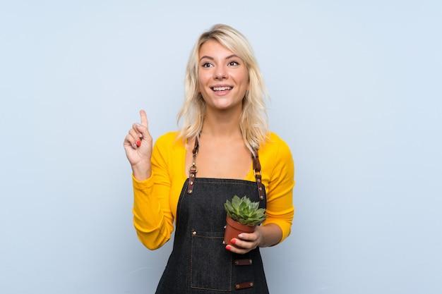 Jovem mulher loira sobre fundo isolado, tomando um vaso de flores e apontando para cima