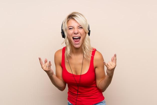 Jovem mulher loira sobre fundo isolado, usando o celular com fones de ouvido e dança