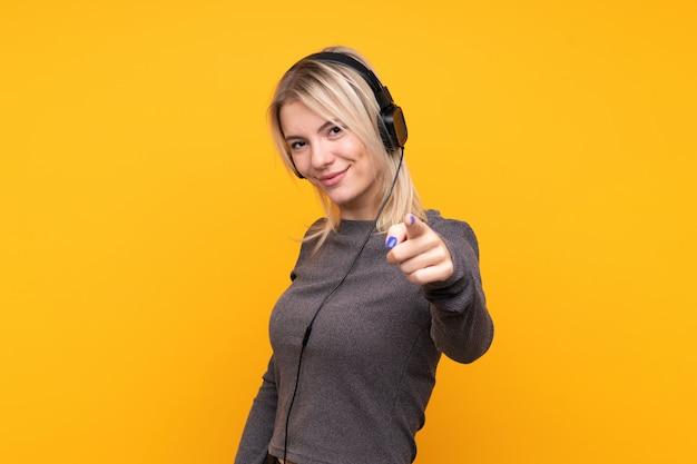 Jovem mulher loira sobre parede amarela isolada ouvindo música e apontando para a frente