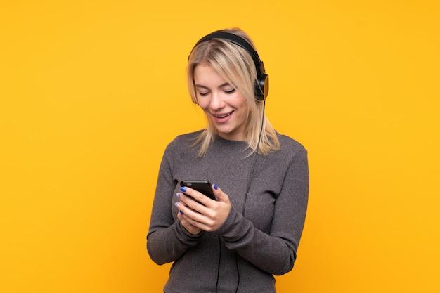 Jovem mulher loira sobre parede amarela isolada ouvindo música e olhando para o celular