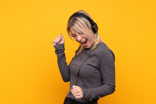 Jovem mulher loira sobre parede amarela isolada, ouvir música e dançar