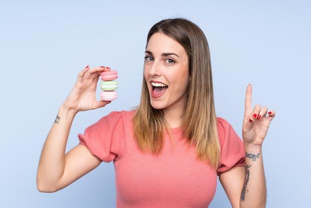 Jovem mulher loira sobre parede azul isolada segurando macarons franceses coloridos e apontando uma ótima idéia