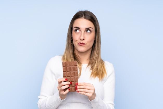 Jovem mulher loira sobre parede azul isolada, tomando uma tablete de chocolate e tendo dúvidas