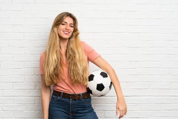 Jovem mulher loira sobre parede de tijolos brancos, segurando uma bola de futebol