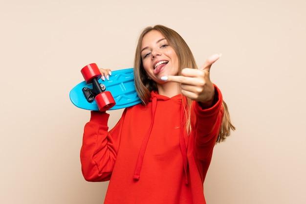 Jovem mulher loira sobre parede isolada com skate