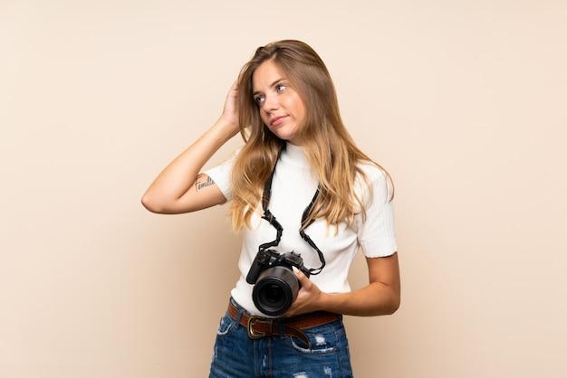 Jovem mulher loira sobre parede isolada com uma câmera profissional e pensando