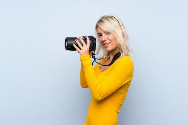 Jovem mulher loira sobre parede isolada com uma câmera profissional