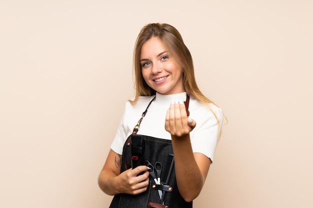 Jovem mulher loira sobre parede isolada com vestido de cabeleireiro ou barbeiro e segurando a máquina de corte de cabelo