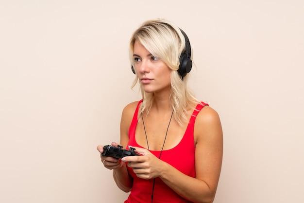 Jovem mulher loira sobre parede isolada, jogando em videogames
