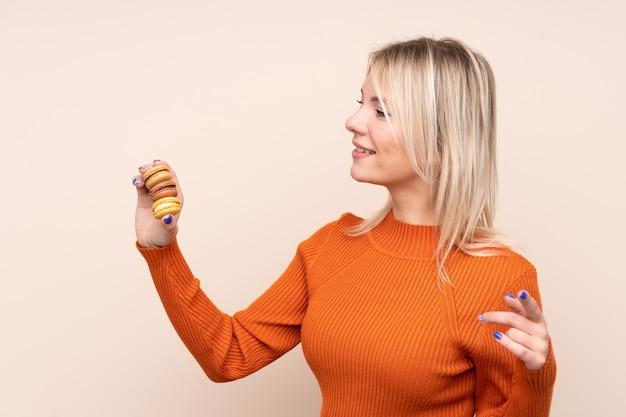 Jovem mulher loira sobre parede isolada segurando macarons franceses coloridos e apontando o lado
