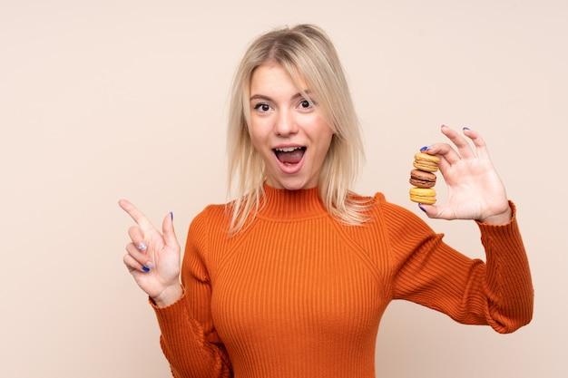 Jovem mulher loira sobre parede isolada segurando macarons franceses coloridos e apontando uma ótima idéia