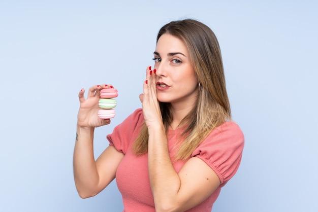 Jovem mulher loira sobre parede isolada segurando macarons franceses coloridos e sussurrando algo