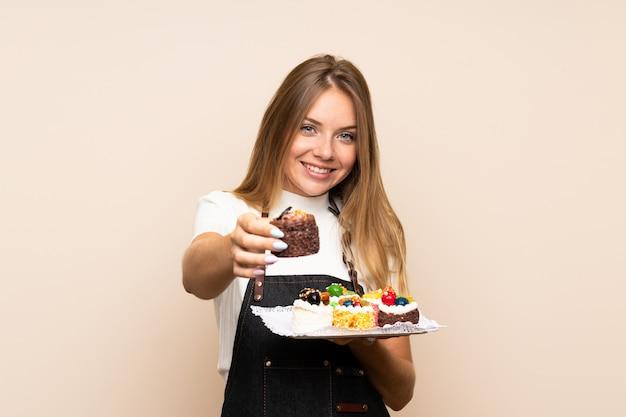 Jovem mulher loira sobre parede isolada segurando mini bolos e oferecendo-o