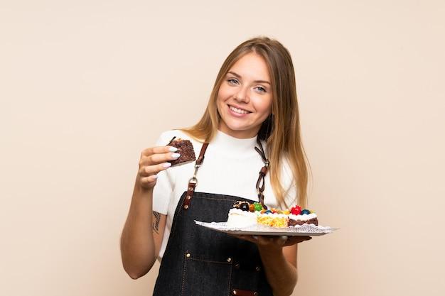 Jovem mulher loira sobre parede isolada segurando mini bolos