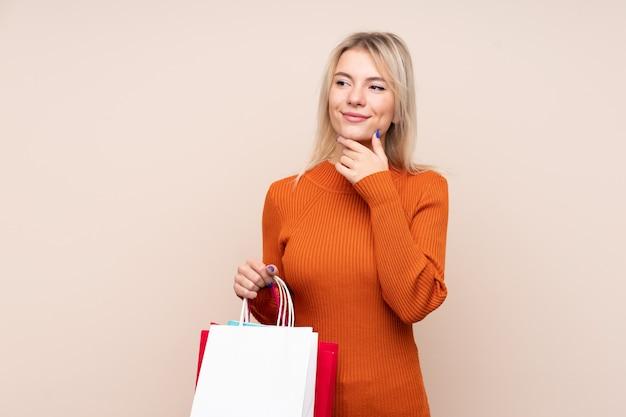Jovem mulher loira sobre parede isolada segurando sacolas de compras e pensando