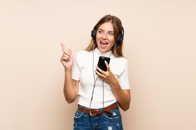 Jovem mulher loira sobre parede isolada, usando o celular com fones de ouvido e cantando