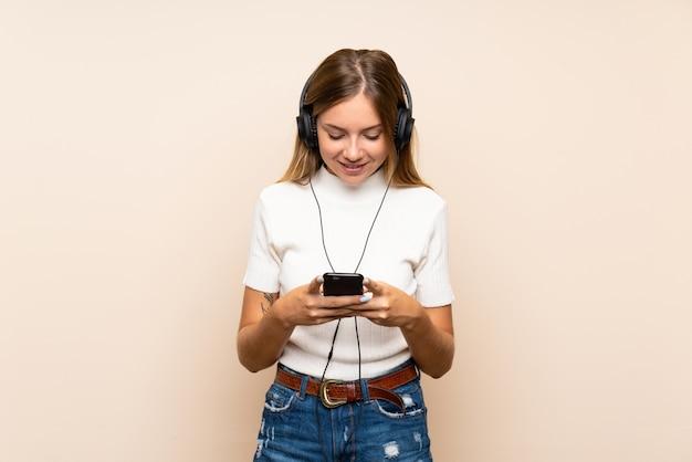 Jovem mulher loira sobre parede isolada, usando o celular com fones de ouvido
