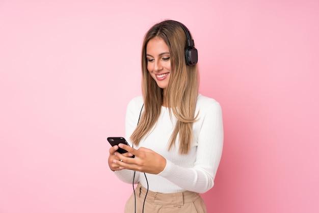 Jovem mulher loira sobre rosa isolado usando o celular com fones de ouvido