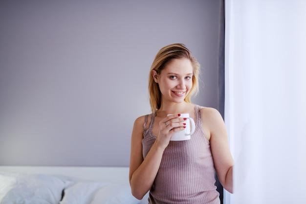 Jovem mulher loira sorridente ao lado da janela e segurando a caneca com café fresco da manhã