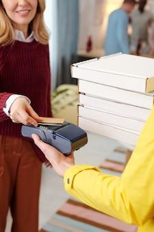 Jovem mulher loira sorridente em roupa casual inteligente, segurando o cartão de crédito na tela da máquina de pagamento na mão de um mensageiro masculino em uniforme amarelo