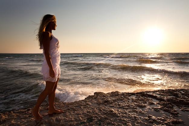 Jovem mulher loira sorridente vestido branco de pé nas rochas e olhando o pôr do sol sobre a água do mar ondulada