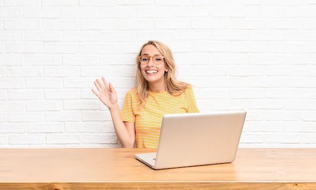 Jovem mulher loira sorrindo alegremente e alegremente, acenando com a mão, dando as boas-vindas e cumprimentando-o ou dizendo adeus usando um laptop