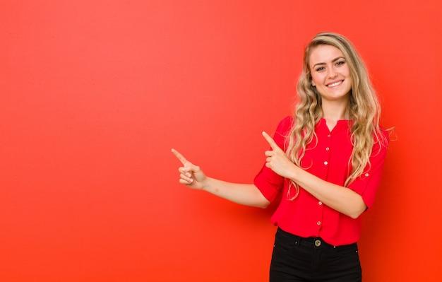 Jovem mulher loira sorrindo alegremente e apontando para o lado e para cima com as duas mãos, mostrando o objeto no espaço da cópia contra a parede vermelha