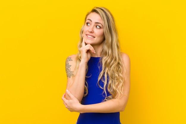 Jovem mulher loira sorrindo alegremente e sonhando acordado ou duvidando, olhando para o lado contra a parede amarela