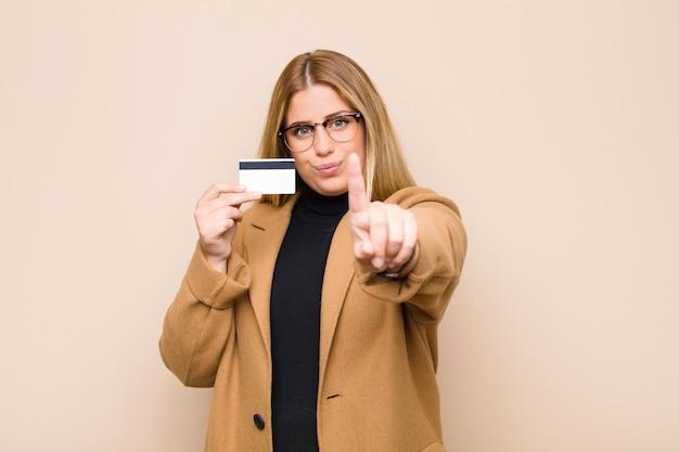 Jovem mulher loira sorrindo com orgulho e confiança, fazendo a pose número um triunfante, sentindo-se como uma líder com cartão de crédito