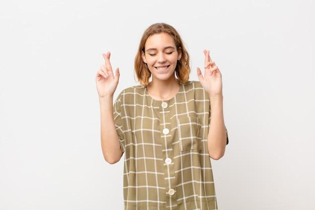 Jovem mulher loira sorrindo e cruzando ansiosamente os dois dedos, sentindo-se preocupado e desejando ou esperando boa sorte contra a parede de cor lisa