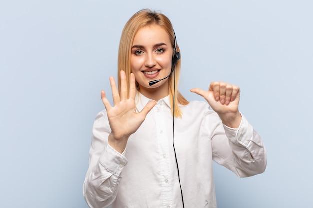 Jovem mulher loira sorrindo e parecendo amigável, mostrando o número seis ou sexto com a mão para a frente, em contagem regressiva
