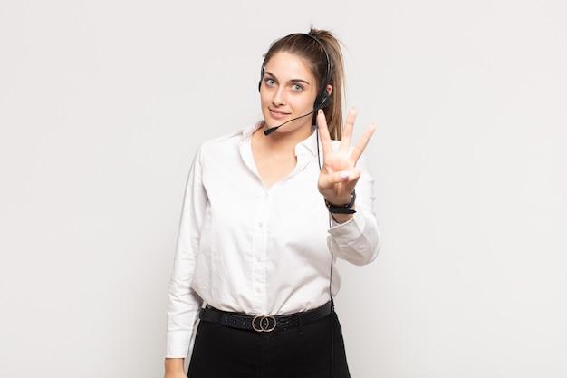 Jovem mulher loira sorrindo e parecendo amigável, mostrando o número três ou terceiro com a mão para a frente, em contagem regressiva