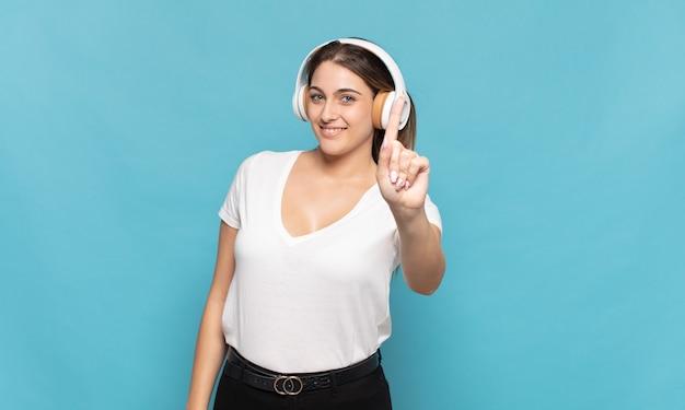 Jovem mulher loira sorrindo e parecendo amigável, mostrando o número um ou primeiro com a mão para a frente, em contagem regressiva