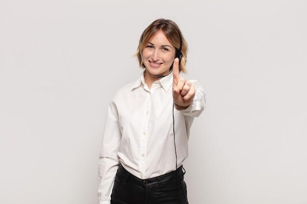 Jovem mulher loira sorrindo e parecendo amigável, mostrando o número um ou primeiro com a mão para a frente, em contagem regressiva Foto Premium