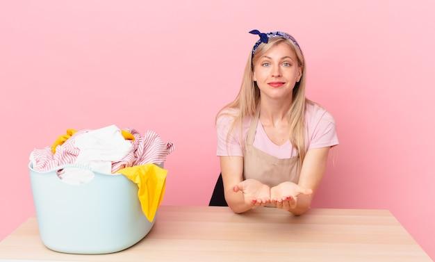 Jovem mulher loira sorrindo feliz com simpáticos e oferecendo e mostrando um conceito. conceito de lavar roupas