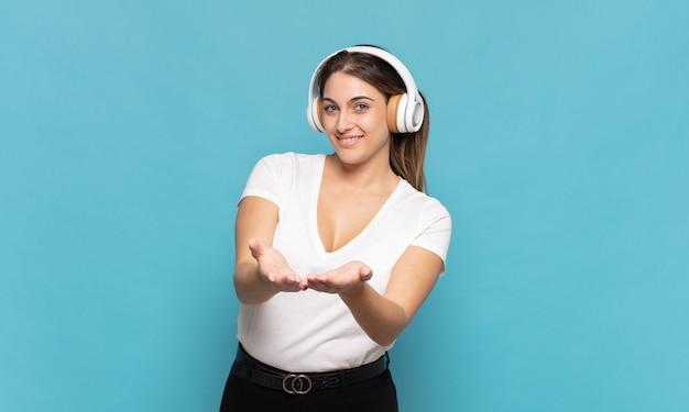 Jovem mulher loira sorrindo feliz com um olhar amigável, confiante e positivo, oferecendo e mostrando um objeto ou conceito