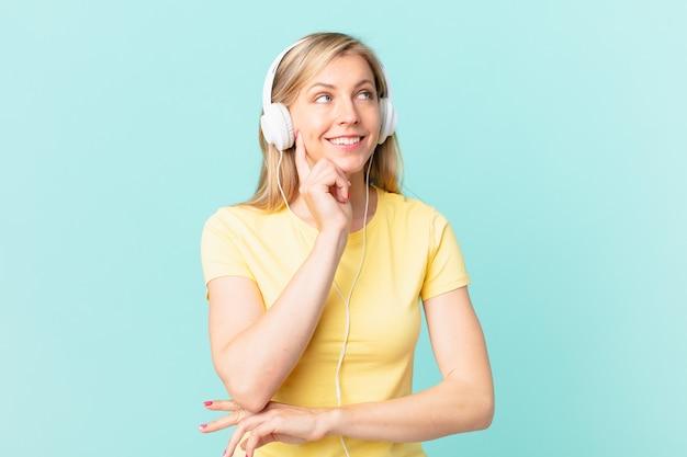 Jovem mulher loira sorrindo feliz e sonhando ou duvidando e ouvindo música.