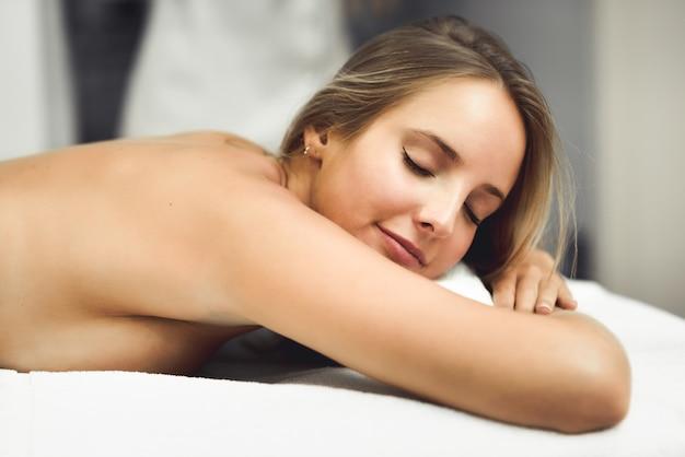 Jovem, mulher loira, tendo massagem e sorrindo no spa