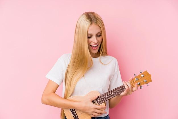 Jovem mulher loira tocando ukelele