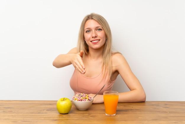 Jovem mulher loira tomando café da manhã aperto de mão depois de bom negócio