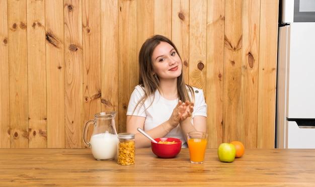 Jovem mulher loira tomando café da manhã aplaudindo