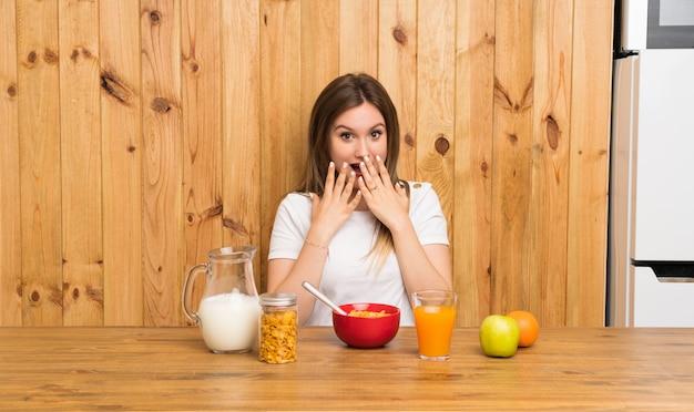 Jovem mulher loira tomando café da manhã com expressão facial de surpresa