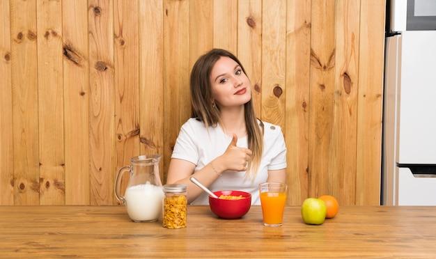 Jovem mulher loira tomando café da manhã dando um polegar para cima gesto