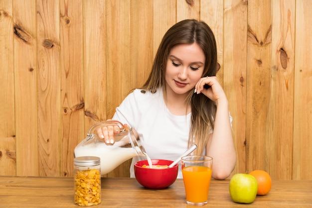 Jovem mulher loira tomando café da manhã