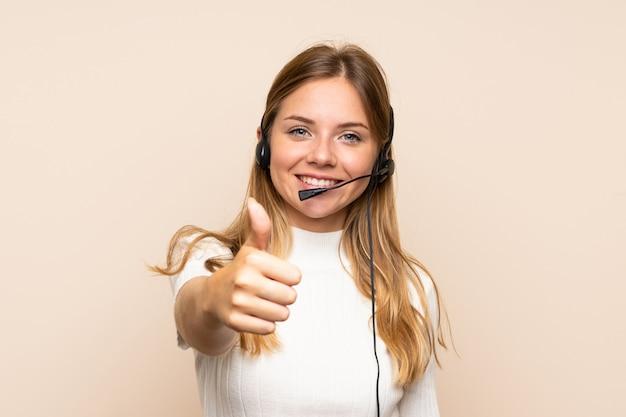 Jovem mulher loira trabalhando com fone de ouvido com o polegar para cima
